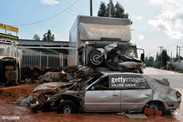 A photo shows damaged vehicles in the town of Mandra northwest of Athens on November 15 after heavy overnight rainfall in the area caused damage and...