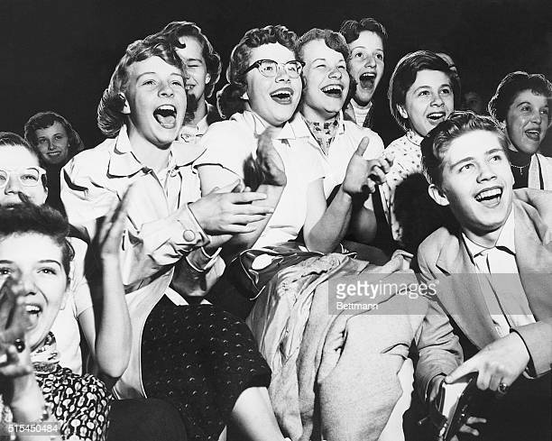 Photo shows eleven teenaged women and one man cheering and laughing at an unmentioned show or event Ca 1950s