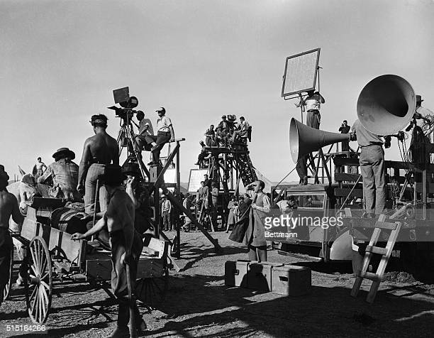 Photo shows filming in progress with the camera crane in the center, on which Cecil B. DeMille himself was watching the work.