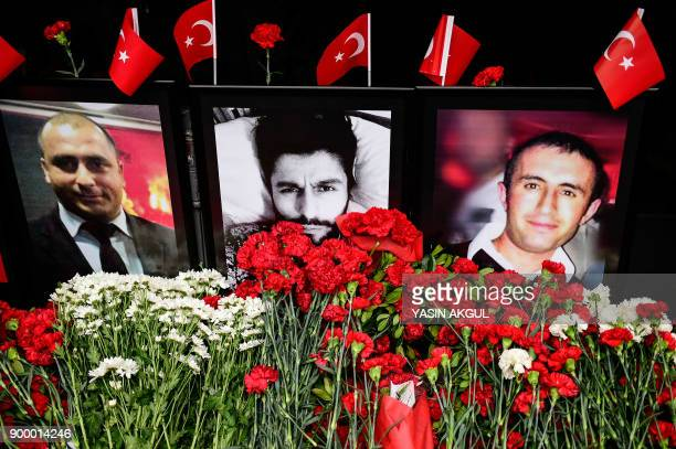 A photo shows flowers left near portraits of victims in front of the Reina nightclub in Istanbul on December 31 a year after an attack on the club...