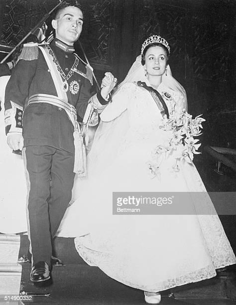 Photo shows Hussein Ibn Talal King of Jordan holding the hand of his first bride Princess Dina daughter of Prince AbdelHamin Aoun of Hijaz during...