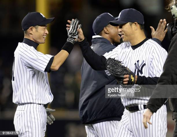 Photo shows Ichiro Suzuki of the New York Yankees giving high fives to teammate Hiroki Kuroda to celebrate the winning game against the Baltimore...