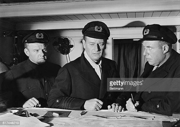 Photo shows John Wayne in a still from the movie 'The Sea Chase' with Alan Hale Jr on his right and an unidentified actor on his left Movie released...