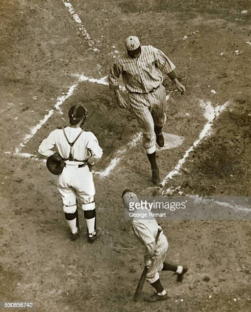 Photo shows Long George Kelly Giants' heavyhitting utility fielder and baseman trotting across hone plate while catcher Muddy Ruel philosophically...