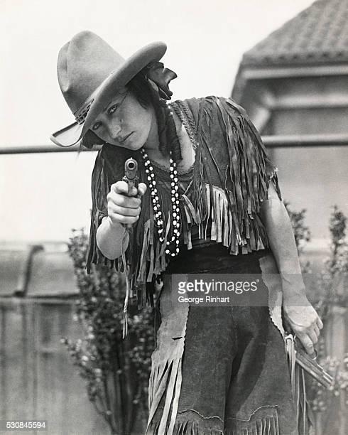 Photo shows Miss Lorena Trickey pointing a gun at the camera