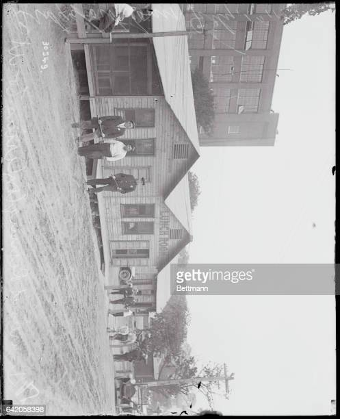 Photo shows one of the newly erected lunch houses under guard of the UM C Co watchmen