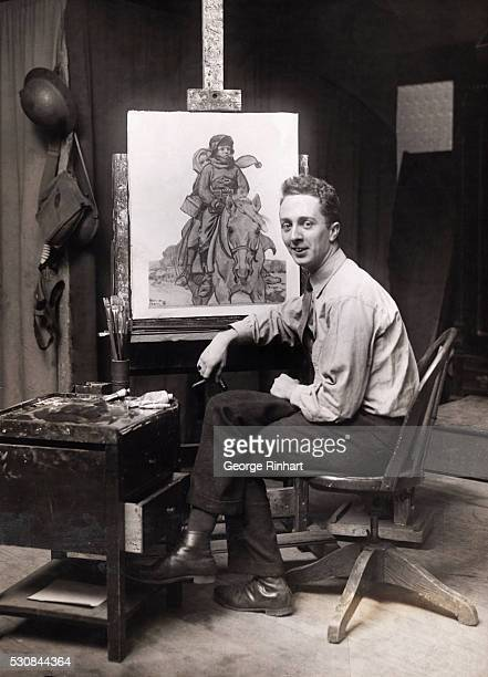 Photo shows painter Norman Rockwell seated in front of one of his paintings.