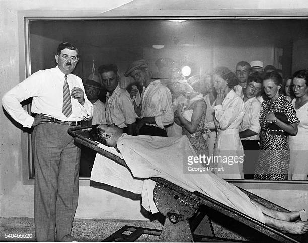Photo shows people filing past a window which displays John Dillinger's corpse on a tilted table