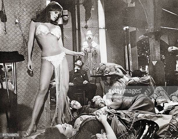 Photo shows Raquel Welch in an exotic bathing suit standing over people sleeping on the ground in this movie still '20th Century Fox resents Stanley...