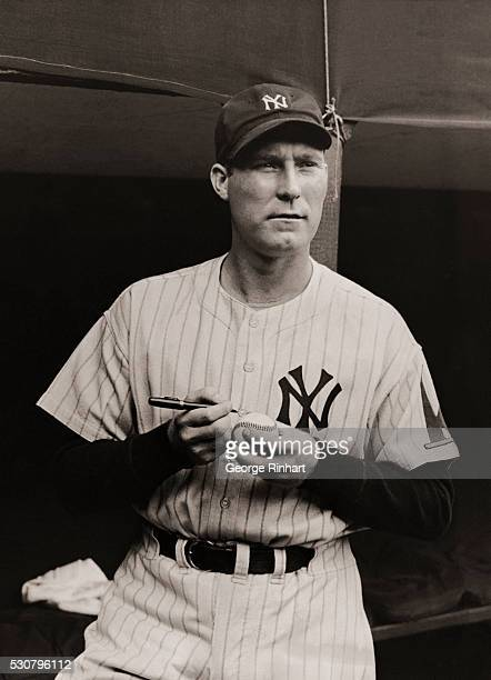 Photo shows Red Ruffing about to autograph a baseball during intermission at the third game of the World Series played at the Yankee Stadium