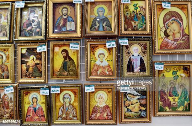 A photo shows religious icons made with amber in an amber shop in Rivne northwestern Ukraine on September 21 2017 Volodymyr Korkosh steps on the...
