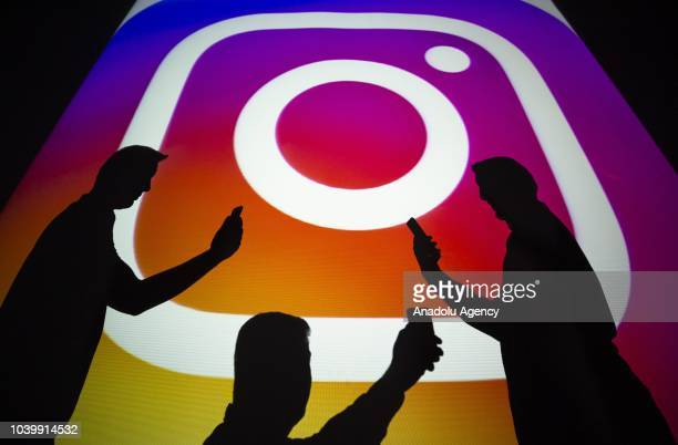 A photo shows silhouttes of men in front of the logo of 'Instagram' social media platform in Ankara Turkey on September 25 2018