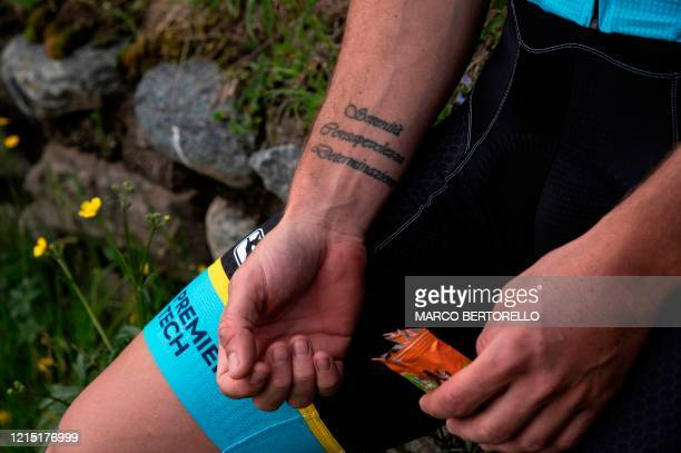 """Photo shows tattoos on the arm of Astana cycling team Italian rider Fabio Felline, reading """"Serenity, Awareness, Determination"""" as he takes a snack..."""