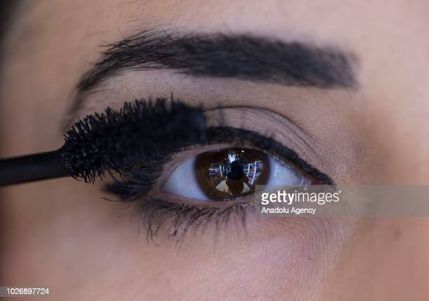 Photo shows the close-up brown eye of a woman getting her eyelashes makeup using mascara at a make-up and cosmetic products shop in Ankara, Turkey on...