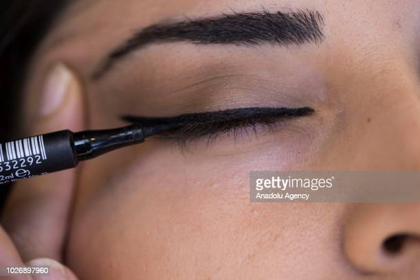 A photo shows the closeup brown eye of a woman getting her eyelashes makeup using eyeliner at a makeup and cosmetic products shop in Ankara Turkey on...