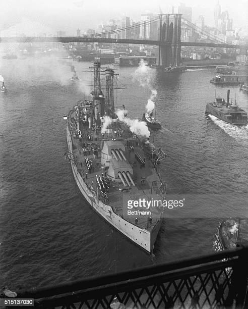 Photo shows the USS Arizona largest and newest of Uncle Sam's sea fighters passing out to sea under the Brooklyn Bridge on her first voyage since...