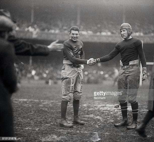 Photo shows two players of an Army vs Navy football game shaking hands