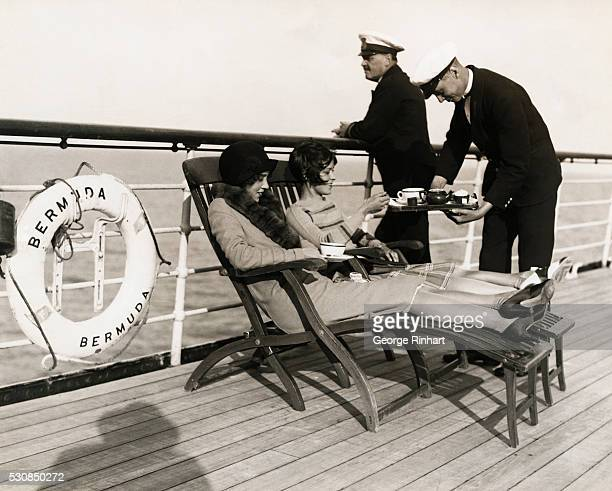 Photo shows two women being served lunch an the launching deck aboard the SS Bermuda.