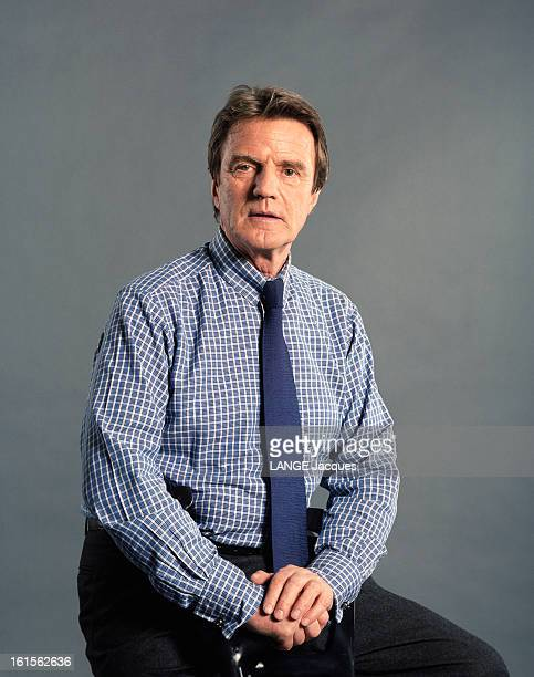 Photo Studio Of Bernard Kouchner Portrait de Bernard KOUCHNER assis cravate bleue et chemise à carreaux