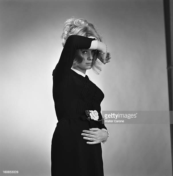 Photo Studio Of Catherine Deneuve Photo studio attitude de Catherine DENEUVE de troisquarts un bras devant le visage vêtue d'une petite robe noire à...