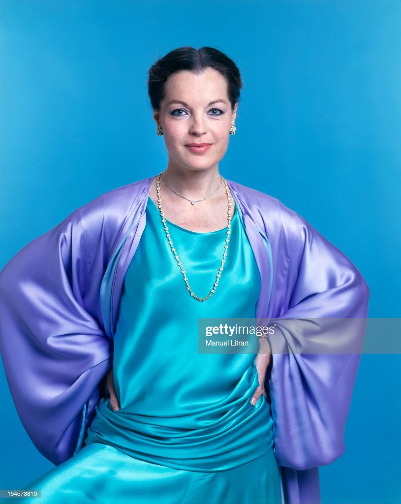 Photo studio Romy Schneider on the occasion of his 40th birthday: plan smiling face of the actress in turquoise blue dress in a purple shawl and Yves Saint Laurent dress with a Van Cleef amp; ARPELS standing hands on hips.