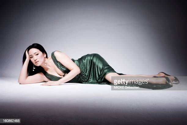 sensual attitude of GONG LI elongated floor dressed in a pleated green dress Roberto Cavalli and lowcut earrings CHOPARD
