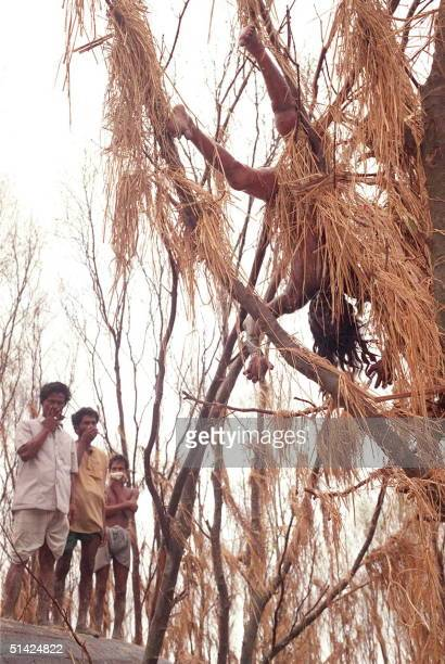 Photo taken 03 May 1991 shows people covering their noses to protect themselves from the stnch of a dead body hanging from a tree near Hatya in the...