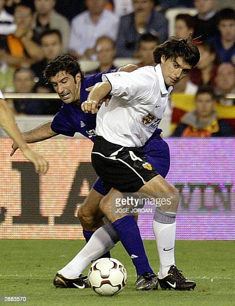 Photo taken 24 May 2003 shows Real Madrid's Luis Figo grappling with Valencia's Argentinian Roberto Ayala in a Liga match at the Mestalla Stadium in...