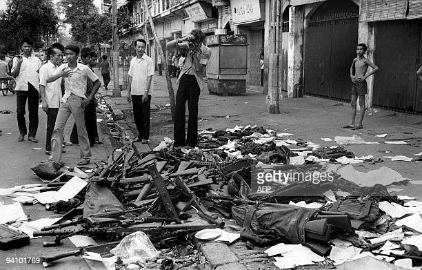 A photo taken 27 May 1975 shows inhabitants looking at US army guns collected in a street of Saigon after the fall of the city The war in Vietnam...