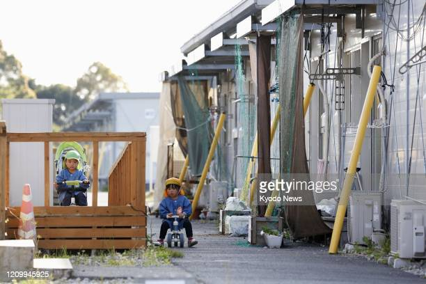 Photo taken April 14 shows children playing at a temporary housing complex in the Kumamoto prefecture town of Mashiki in southwestern Japan for...