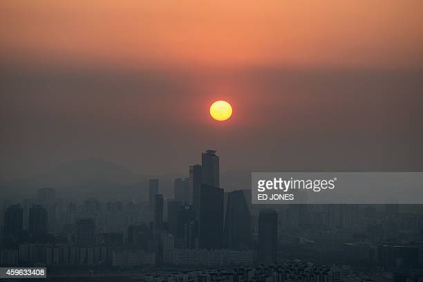 A photo taken at dusk on November 26 2014 shows a general view of the skyline of Seoul shrouded in smog Air quality monitors in Seoul recorded...
