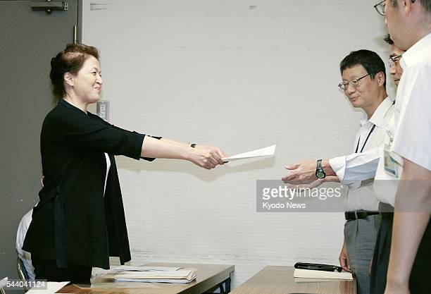 Photo taken at the Osaka municipal office on July 1 shows Song Chong Ji head of an Osakabased group of Korean residents submitting a document to city...