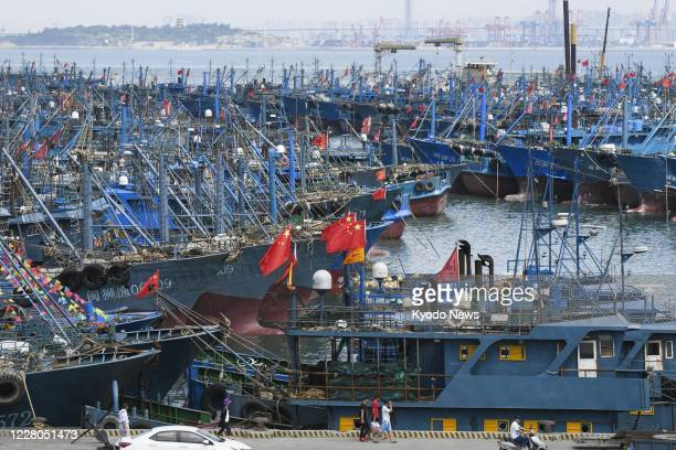 Photo taken Aug 15 shows fishing vessels with Chinese national flags erected at a port in Shishi in Fujian Provence ahead of departure