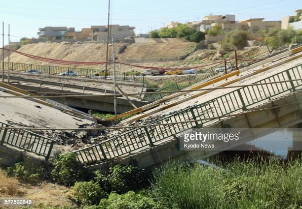 Photo taken Aug 6 shows a destroyed bridge over an arm of the Tigris River in Mosul about a month after the Iraqi government declared victory in the...