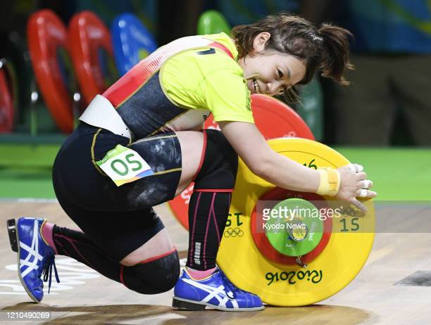 Photo taken Aug. 6 shows Japanese weightlifter Hiromi Miyake stroking her barbell after a successful jerk of 107 kilograms in the women's 48-kilogram...