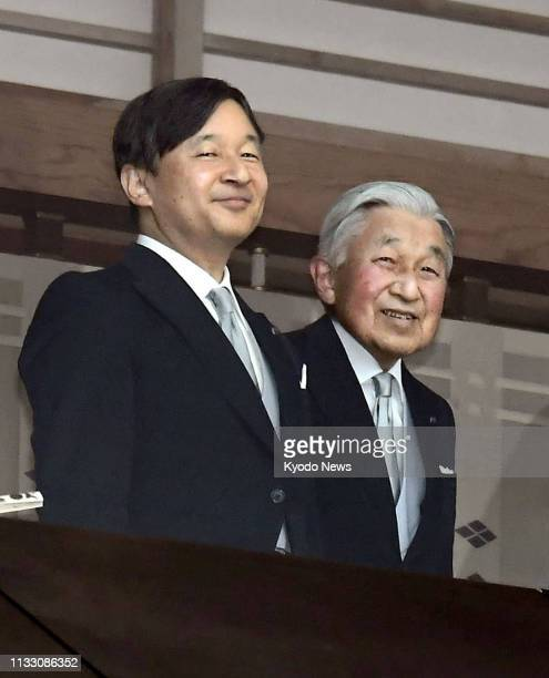 Photo taken Dec 23 shows Japanese Crown Prince Naruhito and Emperor Akihito on a balcony at the Imperial Palace in Tokyo from which they greeted a...