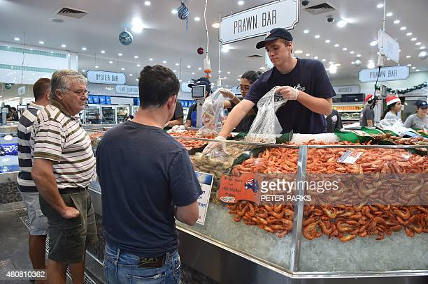 Photo taken early on December 23 2014 shows customers buying cooked prawns at the Sydney Fish Market in Sydney The Sydney Fish Markets opened for its...
