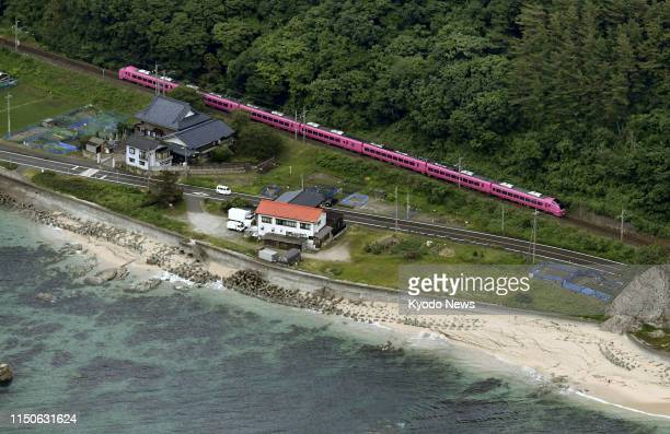 Photo taken from a Kyodo News airplane on June 19 shows a JR Uetsu line train that remains stopped between stations in Murakami, Niigata Prefecture,...