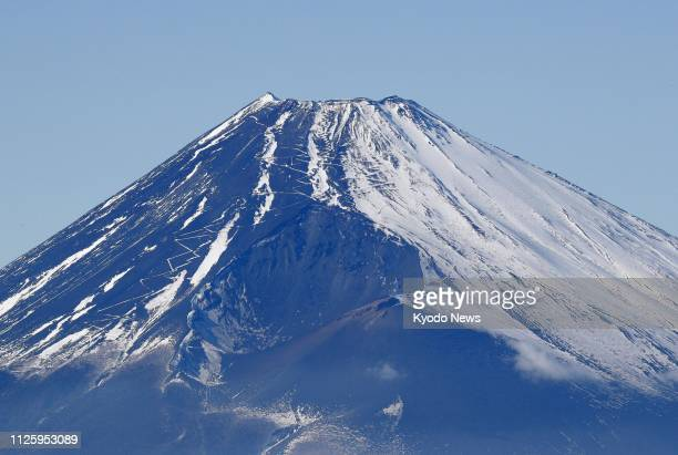 Photo taken from a Kyodo News helicopter above Mishima Shizuoka Prefecture on Feb 18 shows Mt Fuji Japan's highest mountain showing an unusual look...