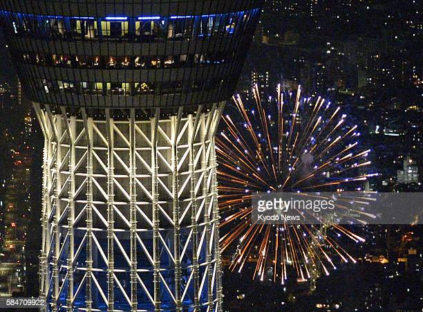 Photo taken from a Kyodo News helicopter on July 30 shows fireworks lighting up the night sky over the Sumida River in Tokyo near the litup 634meter...