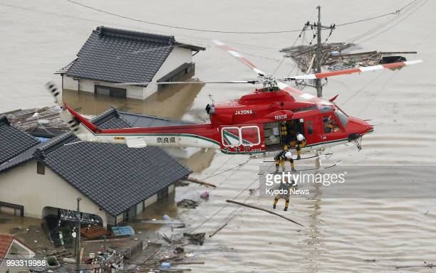 Photo taken from a Kyodo News helicopter on July 7 2018 shows a rescue operation under way in a badly flooded residential area of Kurashiki Okayama...