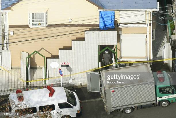 Photo taken from a Kyodo News helicopter on Nov 1 2017 shows an investigator entering the apartment complex where nine dismembered bodies were...
