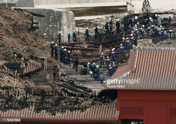 Photo taken from a Kyodo News helicopter on Nov 1 shows police officers and firefighters inspecting Shuri Castle in Naha Okinawa Prefecture southern...