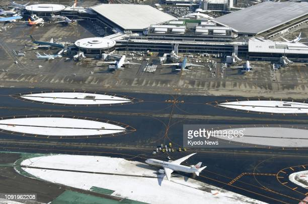 Photo taken from a Kyodo News helicopter shows a Japan Airlines plane that ran off a taxiway after landing at Narita airport east of Tokyo on Feb 1...
