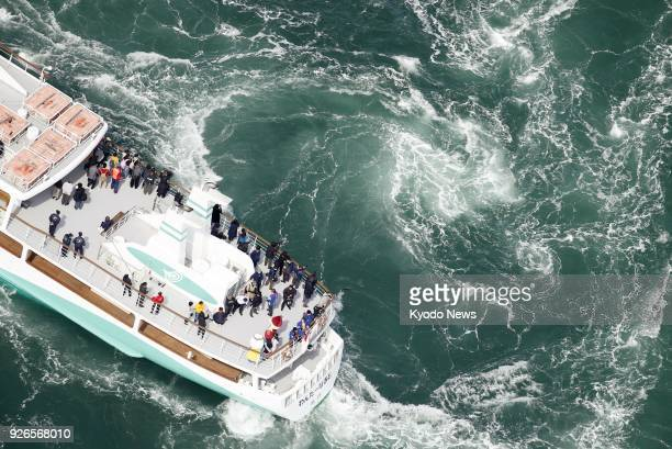 Photo taken from a Kyodo News helicopter shows a sightseeing boat sailing near whirlpools in Naruto Strait Tokushima Prefecture western Japan on...