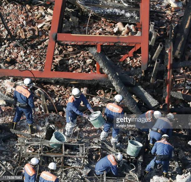 Photo taken from a Kyodo News helicopter shows firefighters in Naha Okinawa Prefecture southern Japan on Nov 1 inspecting the area where the Seiden...