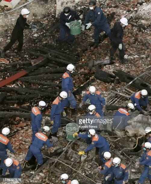 Photo taken from a Kyodo News helicopter shows police officers and firefighters in Naha Okinawa Prefecture southern Japan on Nov 1 inspecting the...