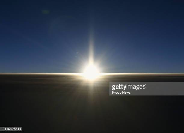 Photo taken from a Kyodo News plane flying about 12000 meters above Tokyo shows the sun rising at 451 am May 1 the first day of Reiwa Japan's new...