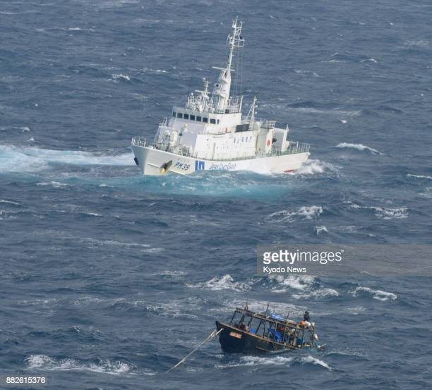 Photo taken from a Kyodo News plane on Nov 29 shows a Japan Coast Guard vessel approaching a North Korean fishing boat near an uninhabited island off...