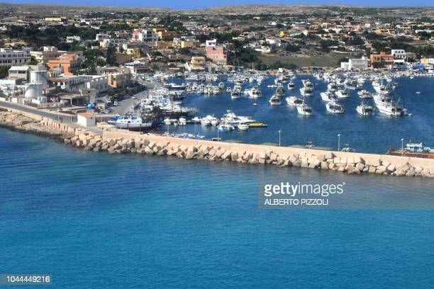 A photo taken from behind the plane window of a commercial flight shows the touristic port of Lampedusa on September 25 2018 Five years after the...